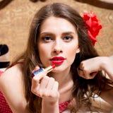 El retrato del primer de la muchacha modela sexual atractiva atractiva con la flor roja en pelo dibuja los labios abiertos del lá Imagen de archivo libre de regalías