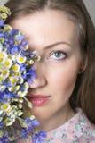 El retrato del primer de la mujer elegante hermosa joven con la primavera magnífica florece Las flores cubren la mitad de la cara Fotos de archivo libres de regalías