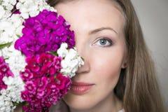El retrato del primer de la mujer elegante hermosa joven con la primavera magnífica florece Las flores cubren la mitad de la cara Fotografía de archivo