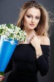 El retrato del primer de la mujer joven hermosa con joyería de lujo y perfectos componen sostener el ramo Foto de archivo
