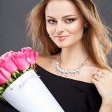 El retrato del primer de la mujer joven hermosa con joyería de lujo y perfectos componen sostener el ramo Imágenes de archivo libres de regalías