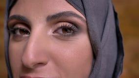 El retrato del primer de la mujer musulmán de mediana edad tranquila en hijab con maquillaje brillante que mira en cámara encendi metrajes