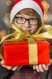 El retrato del primer de la tenencia linda de la muchacha envolvió el regalo de Navidad Fotografía de archivo
