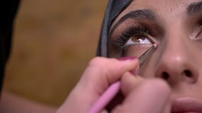 El retrato del primer de las manos femeninas que hacen maquillaje del ojo usando el pequeño cepillo para la señora musulmán en hi metrajes