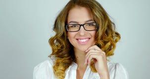 El retrato del primer de un modelo femenino joven con las lentes es de presentación y sonriente en estudio metrajes