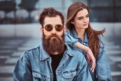 El retrato del primer de un par del inconformista de un varón barbudo brutal en gafas de sol y su novia se vistió en chaquetas de fotos de archivo libres de regalías
