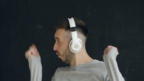 El retrato del primer del hombre divertido joven pone los auriculares y el baile loco mientras que escuche la música en fondo neg almacen de video
