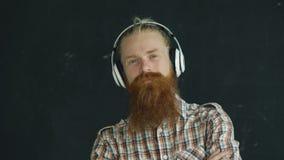 El retrato del primer del hombre joven barbudo pone los auriculares y el baile mientras que escuche la música en fondo negro almacen de video