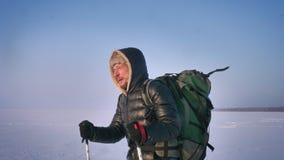 El retrato del primer en perfil del backpacker cansado con los palillos de la montaña y el bolso enorme camina lentamente hacia l almacen de metraje de vídeo