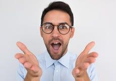 El retrato del primer del gesto masculino joven sin afeitar sorprendido con las manos y abre la boca con la expresión alegre, exp foto de archivo libre de regalías