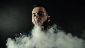 El retrato del primer del hombre barbudo exhala el vapor y parecer derecho en la cámara almacen de video