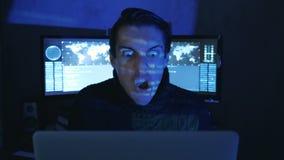 El retrato del programador enojado del pirata informático grita y muestra la agresión mientras que trabaja en el ordenador Tensió almacen de video