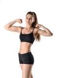 El retrato del recorte del modelo femenino que doblaba su bíceps que se colocaba de lado se vistió en ropa deportiva foto de archivo