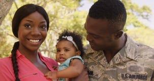 El retrato del soldado americano está sonriendo con su esposa y su bebé almacen de video