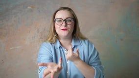 El retrato del tamaño extra grande atractivo en mujer de los vidrios liga y tienta aislado sobre fondo coloreado Concepto de emoc almacen de video