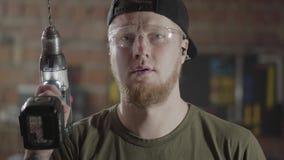 El retrato del trabajador barbudo confiado aumenta el destornillador del taladro y presiona el botón de modo que trabaje Profesi? almacen de video