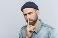 El retrato del varón barbudo serio con mirada atractiva, guarda el finger delantero en los labios, mira con la expresión secreta, imagen de archivo libre de regalías