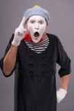 El retrato del varón divertido imita con el sombrero gris y Fotos de archivo libres de regalías