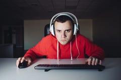 El retrato del videojugador divertido que mira cuidadosamente supervisa su ordenador y los videojuegos el jugar imagenes de archivo