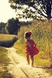 El retrato del vintage de la niña linda corre en un campo del verano imagen de archivo