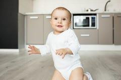 El retrato divertido del pequeño bebé feliz con marrón observa la sonrisa, jugar en cocina, la colocación en rodillas e ir a fotos de archivo