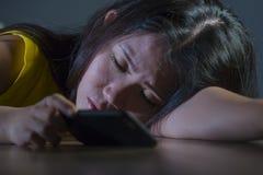 El retrato dramático asustó y subrayó la muchacha adolescente coreana asiática o a la mujer joven con el teléfono móvil que sufrí Fotos de archivo libres de regalías