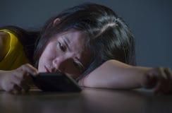 El retrato dramático asustó y subrayó la muchacha adolescente coreana asiática o a la mujer joven con el teléfono móvil que sufrí Fotografía de archivo