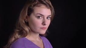 El retrato en perfil de la mujer caucásica rubia linda da vuelta a la cámara y mira seriamente en él en fondo negro metrajes