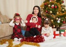 El retrato feliz de la familia en la decoración de la Navidad, concepto de las vacaciones de invierno, adornó el árbol de abeto y Fotografía de archivo