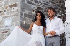 El retrato feliz de los recienes casados de un par plantea el abarcamiento junto cerca de la pared gris vieja en Grecia Copie el  foto de archivo