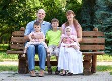 El retrato feliz en al aire libre, grupo de la familia de cinco personas se sienta en banco de madera en parque de la ciudad, la  Fotos de archivo libres de regalías