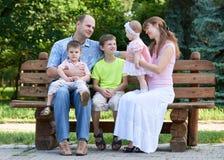 El retrato feliz en al aire libre, grupo de la familia de cinco personas se sienta en banco de madera en parque de la ciudad, la  Foto de archivo
