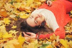 El retrato feliz sonriente de la muchacha, mintiendo en hojas de otoño, se relaja con los ojos cerrados, vestidos en suéter de la Fotos de archivo