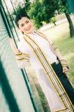 El retrato femenino de la graduación en vestido académico está mirando forwa Fotos de archivo