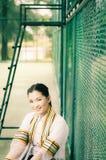 El retrato femenino de la graduación en vestido académico está mirando forwa Imagen de archivo