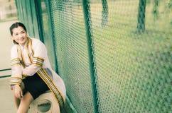 El retrato femenino de la graduación en vestido académico está mirando forwa Foto de archivo libre de regalías