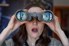 El retrato frontal de la mujer joven chocada es espía hacia fuera la ventana con los prismáticos Imágenes de archivo libres de regalías