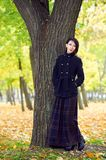 El retrato hermoso de la muchacha que coloca el árbol cercano en el otoño al aire libre, parque de la ciudad con amarillo se va e Imagen de archivo
