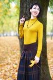 El retrato hermoso de la muchacha que coloca el tronco de árbol cercano en el otoño al aire libre, parque de la ciudad con amaril Fotografía de archivo libre de regalías