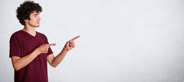 El retrato horizontal del adolescente rizado hermoso tiene pelo oscuro quebradizo, lleva la ropa informal, se coloca oblicuo y la Fotografía de archivo