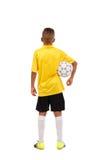 El retrato integral de un deportista joven retrocede y sostiene una bola aislada en el fondo blanco Imagenes de archivo