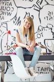 El retrato integral del adolescente feliz con el monopatín que se sienta en estudio presenta en casa Imágenes de archivo libres de regalías