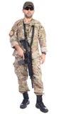 El retrato integral del hombre joven en ejército viste llevar a cabo un weap imagenes de archivo