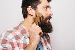 El retrato lateral del hombre caucásico hermoso con sonrisa divertida del bigote y peina el suyo grande Fotografía de archivo libre de regalías