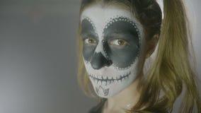 El retrato maléfico de la muñeca de un Halloween poseyó a la mujer con maquillaje en la cara y los ojos grandes que miraban la pa almacen de video