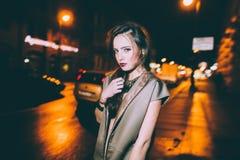 El retrato moreno magnífico atractivo de la muchacha en ciudad de la noche se enciende Imagenes de archivo