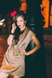 El retrato moreno magnífico atractivo de la muchacha en ciudad de la noche se enciende Fotografía de archivo