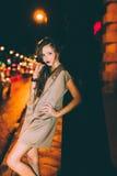 El retrato moreno magnífico atractivo de la muchacha en ciudad de la noche se enciende Foto de archivo libre de regalías