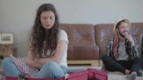 El retrato ofendi? a la mujer rizada que se sentaba en la maleta en primero plano mientras que su marido feliz en el sombrero que almacen de metraje de vídeo
