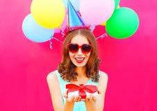 El retrato que la mujer sonriente feliz en un casquillo del cumpleaños sostiene una caja de regalo encendido entrega un rosa colo Imagen de archivo libre de regalías
